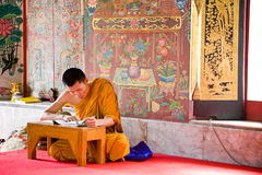 Buddhist monk. A buddhist monk in Bangkok is studying a book in the temple Royalty Free Stock Images