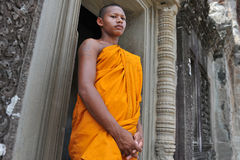 Buddhist Monk. A Buddhist monk waits for alms in a doorway of the historic Angkor Wat temple on July 11, 2012 in Angkor, Cambodia. There are estimated to be more Royalty Free Stock Image