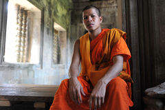Buddhist Monk. A Buddhist monk rests in a corridor of the historic Angkor Wat temple on July 11, 2012 in Angkor, Cambodia. There are estimated to be more than 50 Royalty Free Stock Images