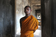 Buddhist Monk. A Buddhist monk waits for alms in a corridor of the historic Angkor Wat temple on July 11, 2012 in Angkor, Cambodia. There are estimated to be Stock Images