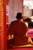 Buddhist Monk. The back of a buddhist monk dressed in orange, sitting praying inside a temple Royalty Free Stock Photography