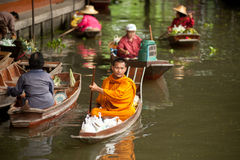 Buddhist monk is the alms in Dam Nuan Saduak floating market in M Royalty Free Stock Photography