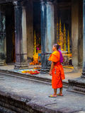 Buddhist Monk in Angkor Wat. Buddhist Monk in traditional costume standing in the temple complex of Angkor Wat, Cambodia. It is the largest religious monument in Royalty Free Stock Images
