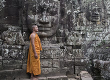 Angkor Wat, Cambodia, Buddhist Monk and stone faces at the Bayon temple Stock Photography
