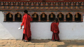 Buddhist monk in bhutan and the prayer wheels stock video footage