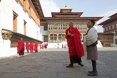 Buddhist monk and bhutanese man at the Trashi Chhoe Dzong, Thimphu, Bhutan Royalty Free Stock Photo