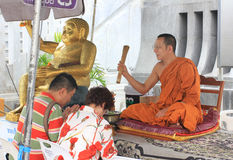 Buddhist monk blessing people ouside some buddhist temple, Thailand Royalty Free Stock Photo