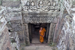Buddhist monk, Buaphon Temple, Angkor Wat, Cambodia. Young Buddhist monk in orange robes standing in doorway of Buaphon Temple in Angkor Wat, Cambodia Stock Image