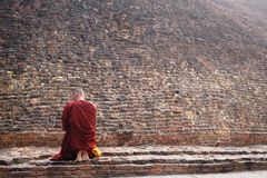 Buddhist monk at Buddha's cremation stupa in a foggy morning, Kushinagar, India Stock Image