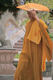 Buddhist monk, Cambodia. Buddhist monk using a folding fan hiding from the sun Stock Photo