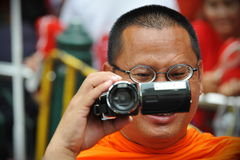 Buddhist Monk with Camcorder. A Buddhist monk uses a camcorder to video a large Red Shirt rally on May 19, 2013 in Bangkok, Thailand. Protesters gathered in royalty free stock photos