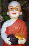 Buddhist Monk Charity Box. Buddhist Monk holding a black charity box or alm wearing yellow glasses with orange robe and red lips, all made of resin Stock Images