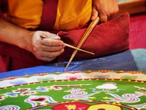 Buddhist monk create drawing mandala with multicolor sands selective focus on hands