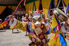 Buddhist monk dance at Paro Bhutan Festival. Buddhist Monk holding a drum at colourful mask dance at yearly buddhism Paro Tsechu festival in Bhutan monastery royalty free stock image