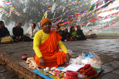 A Buddhist monk does religious rituals in front of Mayadevi temple. On February 08, 2014 in Lumbini, Nepal. Mayadevi temple is the birthplace of Gautama Buddha stock photo