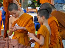 Buddhist young monks doing handcrafts in the temple yard. Buddhist monk doing handcrafts in the temple yard. Young Buddhist monks in a Buddhist monastery in royalty free stock photography