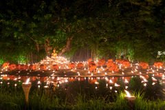Buddhist monk fire candles to the Buddha with beautiful water re Stock Photos