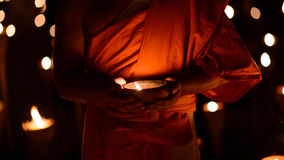Buddhist monk hands holding candle cup in dark Stock Image