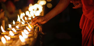 Buddhist monk hands lighting candle lighting candle in dark Royalty Free Stock Image