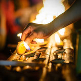 Buddhist monk hands lighting candle lighting candle in dark Royalty Free Stock Photography