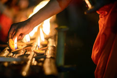 Buddhist monk hands lighting candle lighting candle in dark Stock Images