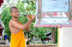 Buddhist monk, hitting the Bell in the temple. Stock Photo