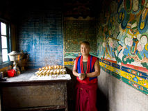 Buddhist monk lighting candles in a monastery Royalty Free Stock Photos