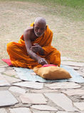 Buddhist monk in Lumbini, Nepal. Monk in temple preaching and waiting for offerings Stock Image