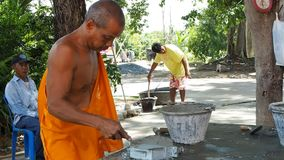 A Buddhist monk makes cement tiles stock footage