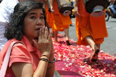 Buddhist Monk Pilgrimage. A woman pays respect to monks from Wat Dhammakaya making a pilgrimage through central Bangkok to mark 2600 years since Buddha's Royalty Free Stock Images