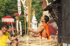 Buddhist monk pin traditional flags on sand pagoda. Stock Photo