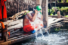 Buddhist monk pours water on Tonle Sap lake Royalty Free Stock Photography