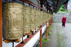 Buddhist monk and prayer wheels in a row Stock Images