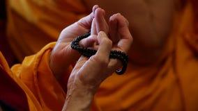 Buddhist monk praying. Hands and beads rosary closeup stock video