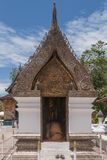 Buddhist monk prays kneeling in a shrine inside the Wat Xieng Thong temple in Luang Prabang, Laos stock image