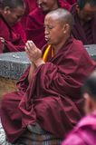 Buddhist monk put his palms together and chanting , Sera monastery , Tibet. Buddhist monk put his palms together and chanting , for he sits on two cushions , we royalty free stock image