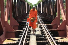 Buddhist monk on a railway bridge in Cambodia. Traditionally, Buddhist monks  leave their monastery everyday morning to go for food. They carry metal food Stock Photo