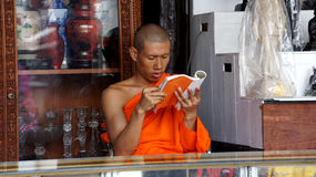 Buddhist monk is reading a book inside a shop Royalty Free Stock Image