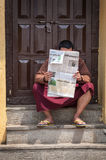 Buddhist monk reading newspaper in Nepal Royalty Free Stock Photos