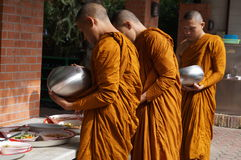Buddhist monk receives food to eat Stock Photo