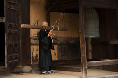 Buddhist monk rings a bell. KAMAKURA, JAPAN - MARCH 23, 2009: Buddhist monk rings a bell before a prayer in a monastery in Kamakura Stock Image