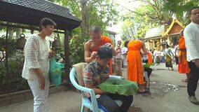 Buddhist monk shaving the head of a boy to prepare him for novice. A Buddhist monk shaving the head of a boy to prepare him for novice. The Ordination Ceremony stock footage