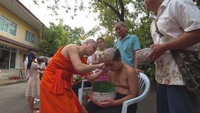 Buddhist monk shaving the head of a boy to prepare him for novice. A Buddhist monk shaving the head of a boy to prepare him for novice. The Ordination Ceremony stock video