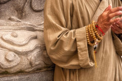 Buddhist Monk. A shoulder down picture of a Buddhist monk wearing prayer beads and tan robes using a smart phone royalty free stock image