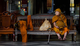 Buddhist Monk sits on a bench at Wat Phra Doi Suthep. CHIANG MAI, THAILAND - NOV 25, 2013: Unidentified Buddhist Monk sits on a bench at Wat Phra Doi Suthep Stock Photography