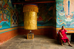 A Buddhist monk sits with a big prayer wheel in the Punakha Fortress Monastery, Paro, Bhutan Royalty Free Stock Image