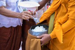 Buddhist monk in south of Vietnam stand in a row waiting people put rice and food offerings in their alms bowl.  Stock Images