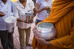 Buddhist monk in south of Vietnam stand in a row waiting people put rice and food offerings in their alms bowl.  Royalty Free Stock Photography