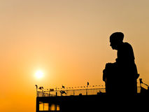 Buddhist monk statue silhouetted Stock Photo