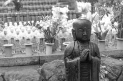 Black and white stone statue of Buddhist monk standing and praying royalty free stock image